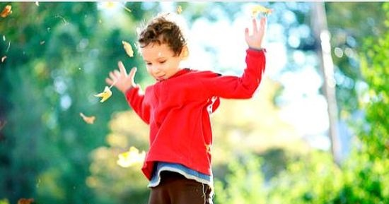 Boy dancing in leaves